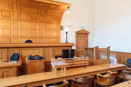 Veduta di un'aula di tribunale con la sedia del giudice, le panche degli avvocati e il banco dei testimoni Archivio Fotografico - 89387469