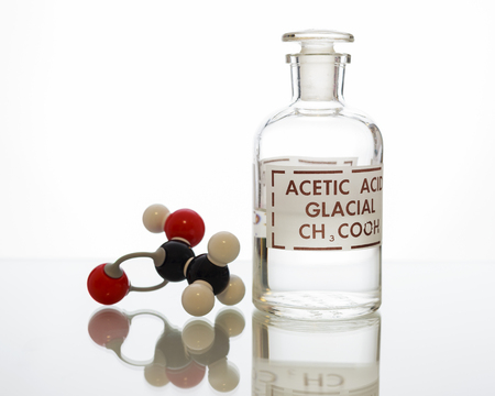 A reagent bottle with acetic acid and the model showing the structure
