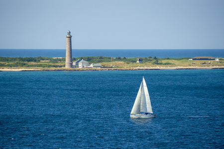 A sail boat passing the lighthouse at Skagen, Denmark.