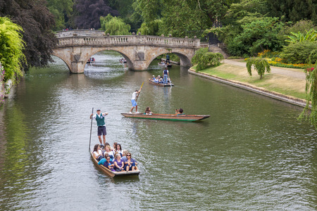 Cambridge, United Kingdom – JULY 11, 2018: Tourists in punts moving along the River Cam near Kings College, taken on July 11 in Cambridge.