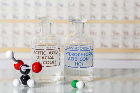 Two reagent bottles containing hydrochloric acid, acetic acid and their molecular models.