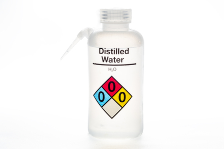 Distilled water bottle used in laboratories with name and safety code. Stockfoto