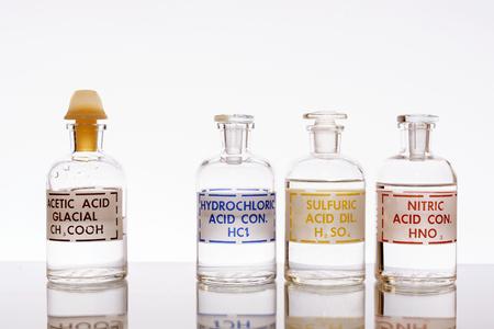 De drie meest voorkomende anorganische zuren en het meest voorkomende organische zuur dat in de chemie wordt gebruikt: zoutzuur, zwavelzuur, salpeterzuur en azijnzuur. Stockfoto