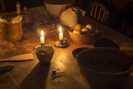 Eggs, flour bag and bowels illuminated by candle on an old wooden table.