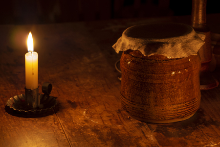 Earthenware flour canister lit by candle on an old table.