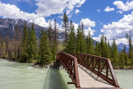 Bridge over an alpine river leading to the mountains, British Columbia, Canada.
