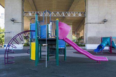 A playground under a bridge in an urban environment.