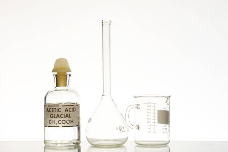 A bottle of glacial acetic acid with a volumetric flask and a beaker.