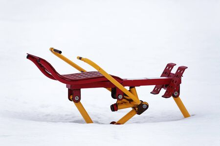 Outdoor exercise equipment covered in snow during the winter.