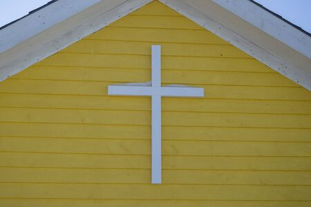 A cross on a yellow exterior wall with snow on top of the cross.