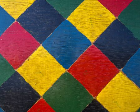 A background with different colored squares painted on wood.