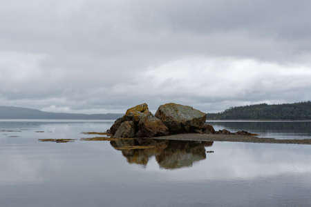 Rock reflection in the ocean on a cloudy day. Archivio Fotografico