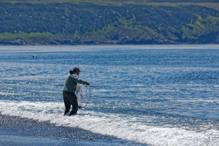 ST. VINCENT'S, NEWFOUNDLAND AND LABRADOR, CANADA - July 8, 2020.  A man using a casting net to catch caplin at the beach, taken on July 8, 2020, in St. Vincent's.