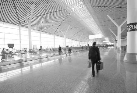 gente aeropuerto: Interior del aeropuerto de Guangzhou futurista con la gente que camina en el desenfoque de movimiento Editorial