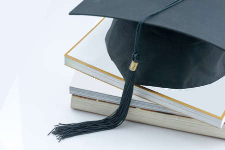 a study: a mortarboard on a book stack on white background. icon image for costs in training and education