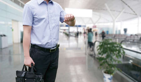 businesstrip: Young Businessman is waiting in the airport waiting hal and he checks the time on his watch. Editorial