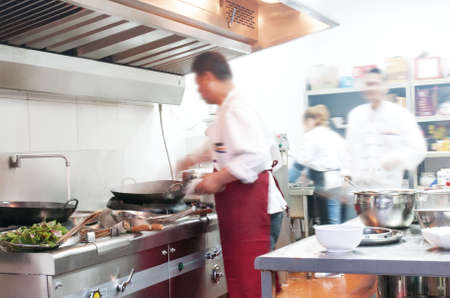 Chef in restaurant kitchen at stove with pan, doing flambe on food Reklamní fotografie - 41427223