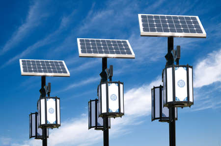 Solar photovoltaic powered lamp posts on the blue skies with sun Imagens