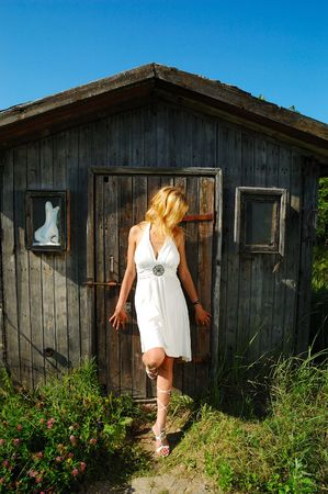 privy: blond woman in white dress standing near wood hut Stock Photo