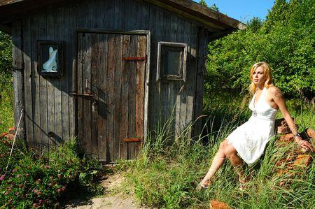 privy: blond woman in white dress sitting near wood hut Stock Photo