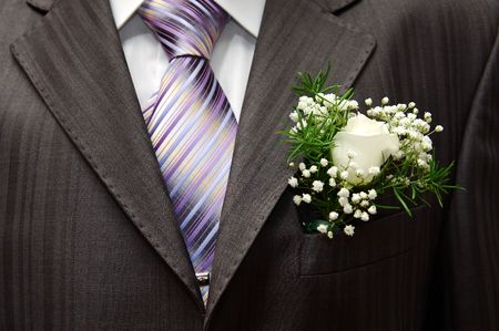 boutonniere: White rose boutonniere on grooms wedding suit