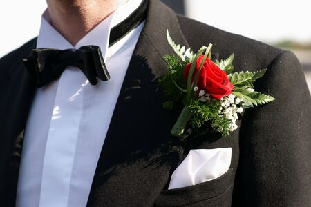 boutonniere: Red rose boutonniere on grooms wedding suit