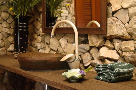 towels wall: Thai style bathroom with stone walls Stock Photo