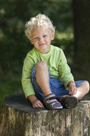 blonde boy sitting on a tree stump Stock Photo - 10879342