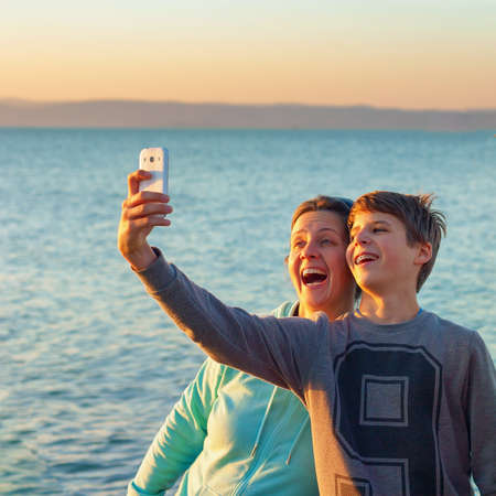 Adult woman taking a selfie with a young boy at the lake Balaton with a smart phone