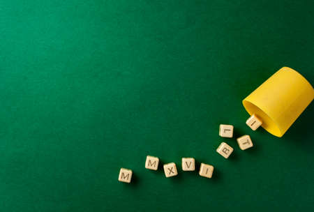 cast: A set of character dices cast from a yellow cup expressing MMXVI Roman 2016 on a plain green background Stock Photo