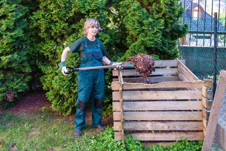 Jeune femelle caucasienne culbutant le compost avec une fourche Banque d'images - 73486291