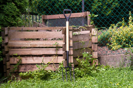 pitch fork at a wooden compost pile frame