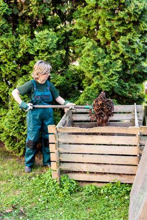 Jeune femelle caucasienne culbutant le compost avec une fourche Banque d'images - 73466969