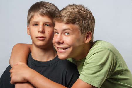 Two boys, one is hugging the other smiling the other face is annoyed Stockfoto