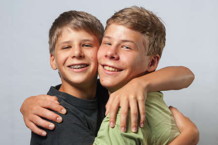 Two boys hugging each other, neutral background Stockfoto