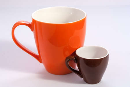 Two cups one big orange and one small brown