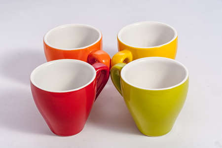 Four small cups on white different colors orange yellow red green Stockfoto