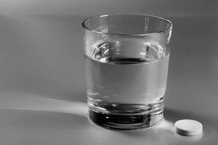 Glass of water on the table and an effervescent pill next to it