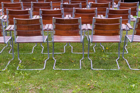 empty, wooden metal chairs of an open air garden theater from back, horizontal