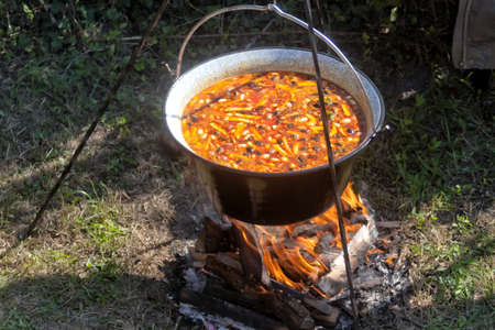 Cooking bean goulash in a caldron on open flame