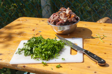 Chopped parsley on a white cutting board on a light colored wooden table