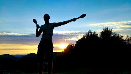 Silhouette of a lean sporty young male exercising outdoor with Indian clubs, with beautiful sunset in the background