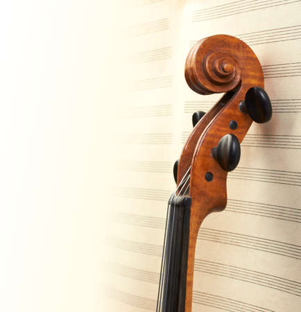 classical music: violin neck on musical sheets background Stock Photo