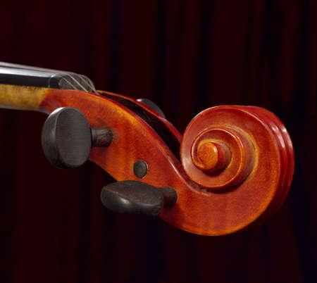 어두운 커튼 배경에 바이올린 목입니다. 나무 클래식 악기 상세