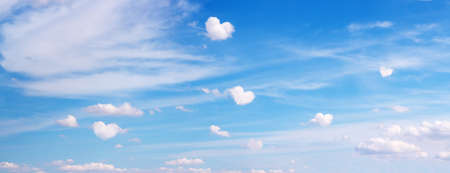 Clouds with heart shape form flying on blue panoramic sky. Romantic, love symbol background Stock Photo