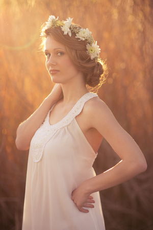 hair tied: Pretty young girl with blond hair tied with a flower crown and white dress. Stock Photo