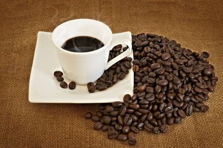 Heap of coffee beans and coffe cup photo