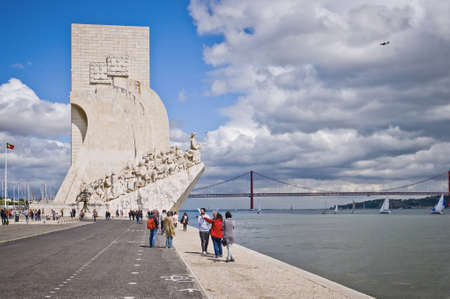 atilde: Lisbon, Belem, Portugal, April 22th 2012  People walking close to the sea, where you can see the Monument to the Discoveries and the 25 April bridge in the back, wile an airplane is landing in the Lisbon airport and boats navigate on the sea