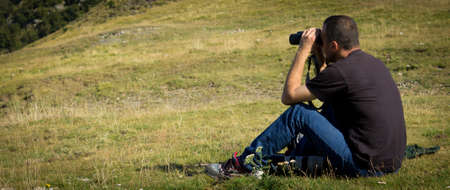 man watching nature with binoculars photo