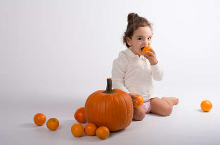 children s feet: little girl playing with orange fruits